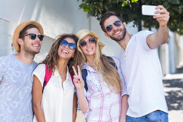 Hanches amis prenant selfie dans la rue