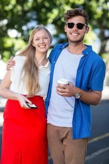 Hanches amis souriant à la caméra dans la rue