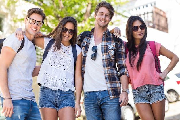 Hanches amis souriants et posant pour la caméra dans les rues