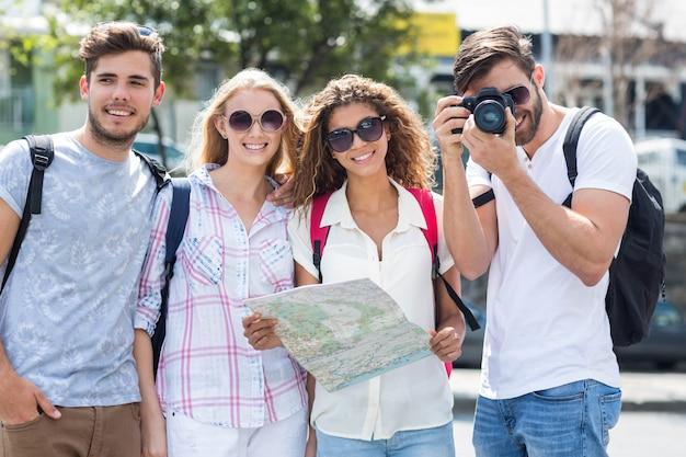 Hanches amis tenant une carte et prenant des photos à la caméra dans la ville
