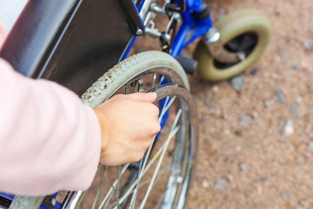Hand handicap femme en roue de fauteuil roulant sur la route dans le parc de l'hôpital en attente de services aux patients. fille paralysée méconnaissable dans une chaise invalide pour les personnes handicapées à l'extérieur. concept de réadaptation.