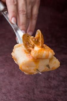 Hand holding ustensile de cuisine avec une portion de palourdes avec merlu sur fond sombre