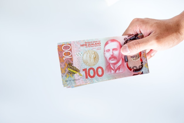Hand holing new zealand 100 billets de dollars sur fond blanc