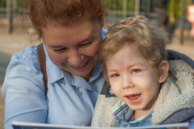 Handicap, un enfant handicapé se repose dans la rue avec sa mère, lisant un livre