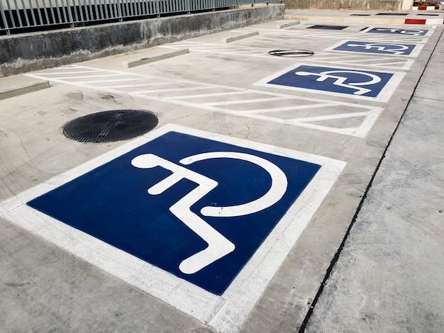 Handicap international (fauteuil roulant) ou symbole de stationnement pour personnes handicapées sur l'espace de stationnement.