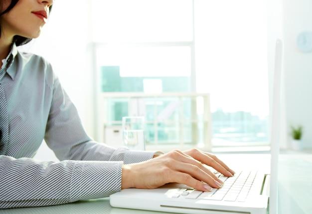 Hands close-up de la jeune femme utilisant un ordinateur portable