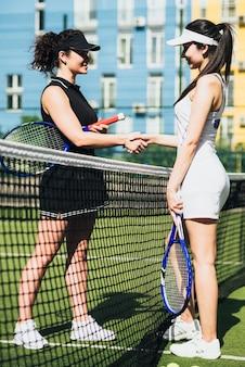Handshaking femmes après avoir joué un match de tennis
