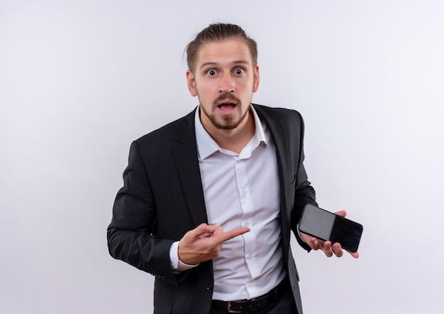 Handsome business man wearing suit holding smartphone pointant avec le doigt sur elle à la surprise et étonné debout sur fond blanc