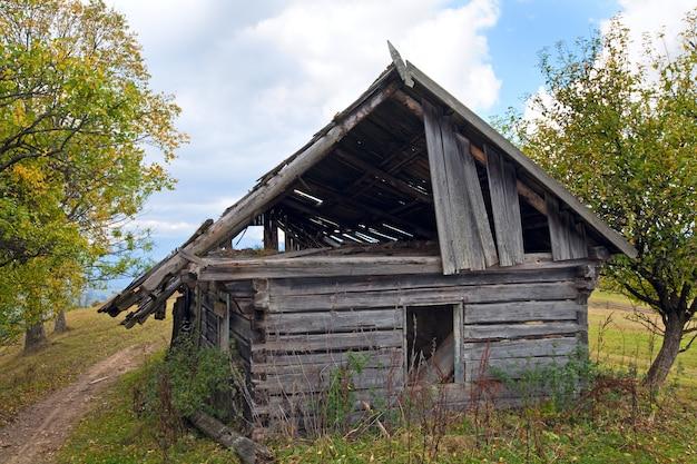 Hangar en bois en ruine sur clairière de montagne