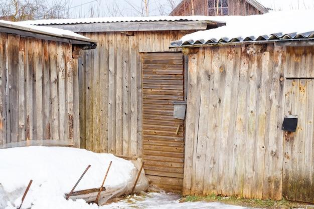 Hangars en bois dans un village d'hiver couvert de neige