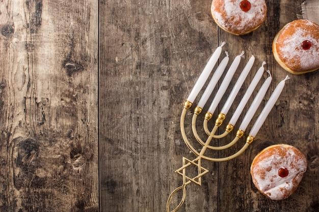 Hanoukka juive, menorah et beignets de soufganiyot sur le fond de la vue de dessus bleue