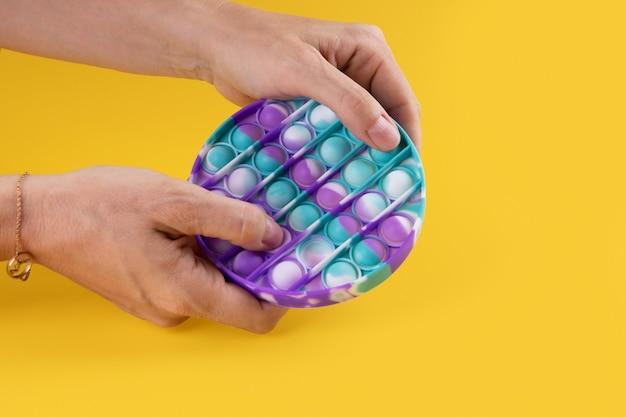 Hans femelle utilisant un jouet popit rond de couleur pastel antistress pour enfants et adultes sur fond jaune. jouet anti-stress sensoriel flexible pop it forme ronde, espace de copie