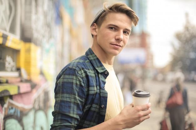 Hansome mec en train de boire un café en marchant dans la rue