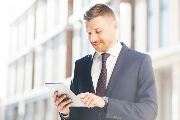 Happpy beau mâle directeur exécutif en costume élégant formel, vérifie le message de revenu via une tablette numérique