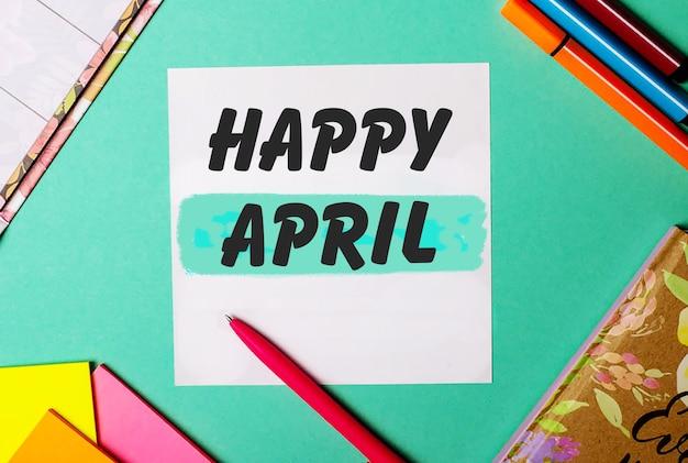 Happy april écrit sur un fond turquoise près d'autocollants, blocs-notes et marqueurs lumineux
