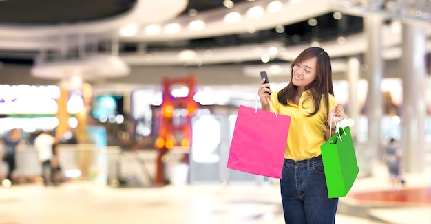 Happy asian girl resive order in paper shopping bag with shopping online by smartphone in new normal digital lifestyle (include clipping path)