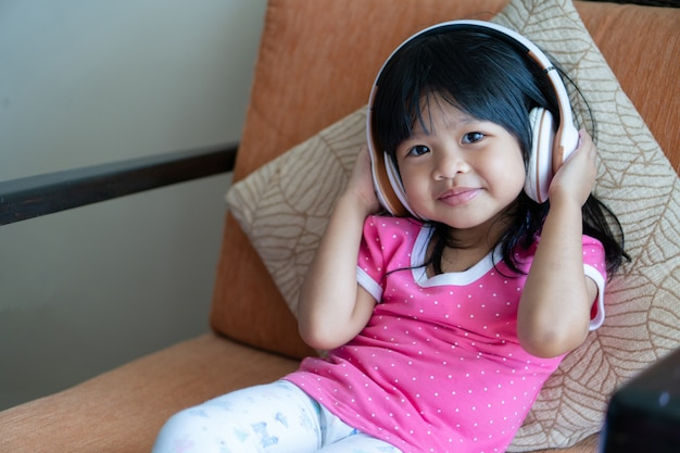 Happy asian girl smiling et aime écouter de la musique dans les écouteurs sur le canapé du salon