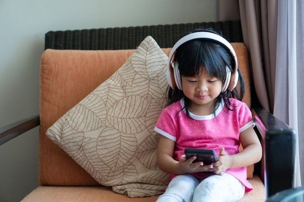 Happy asian girl smiling et aime écouter de la musique dans les écouteurs et tenant un smartphone sur le canapé du salon