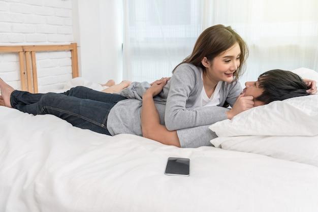 Happy asian lover s'embrasser et s'embrasser sur le lit dans la chambre à la maison