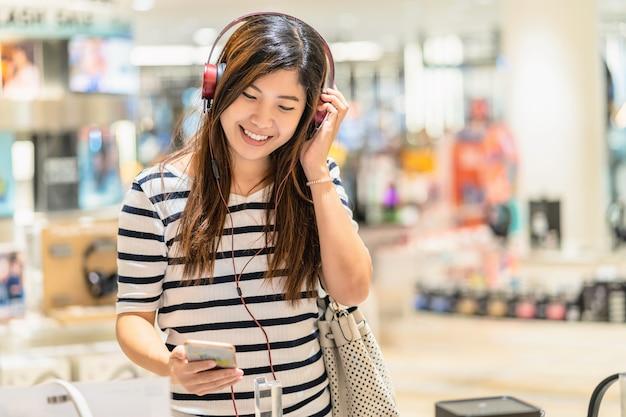 Happy asian woman écoute et teste la technologie écouteur ou casque dans le département st