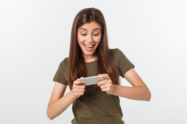 Happy attractive brunette girl joying win dans le jeu vidéo sur smartphone, isolé sur gris