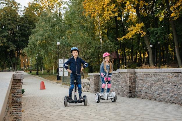 Happy boy and girl ride segways dans le parc par une chaude journée d'automne au coucher du soleil