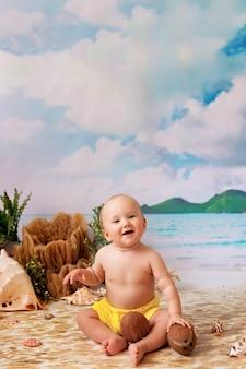 Happy boy est assis en train de bronzer sur une plage de sable avec des palmiers au bord de la mer, enfant jouant avec des noix de coco