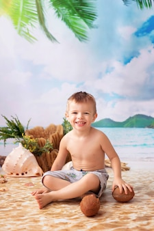 Happy boy est assis en train de bronzer sur une plage de sable avec des palmiers au bord de la mer