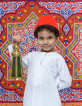 Happy boy avec fez et lanterne célébrant le ramadan