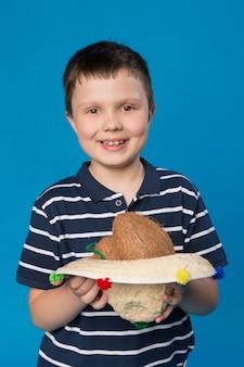 Happy boy holding hat avec une noix de coco à l'intérieur sur fond bleu