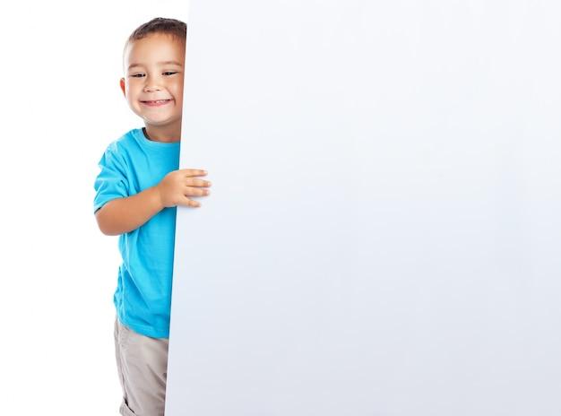 Happy boy posant avec un panneau vide