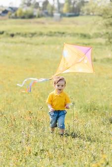 Happy boy s'exécute à l'extérieur avec un cerf-volant