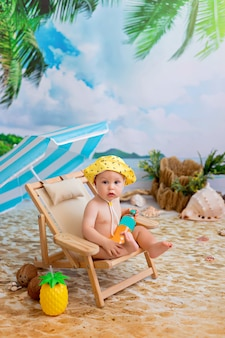 Happy boy en train de bronzer sur une chaise longue en bois sur une plage de sable au bord de la mer sous un parasol