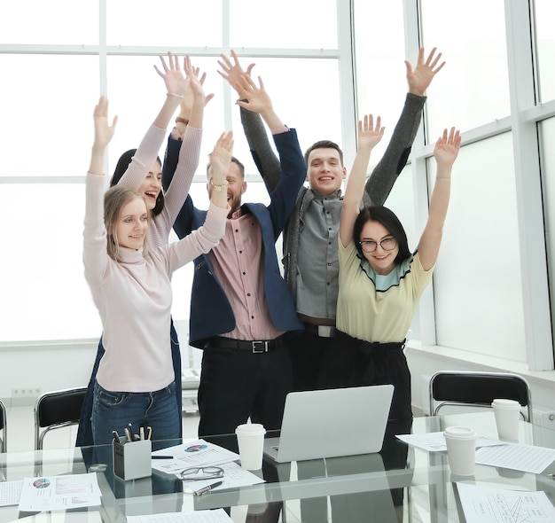 Happy business team debout près du bureau avec les mains vers le haut