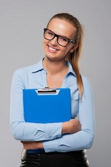 Happy businesswoman holding presse-papiers bleu