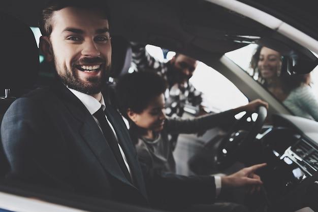 Happy car manager vend un véhicule à une famille afro.