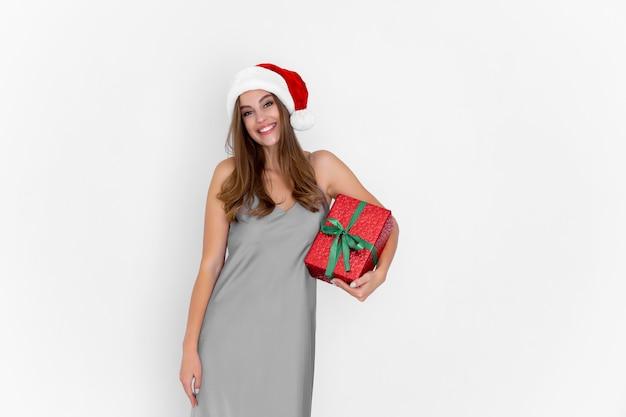 Happy caucasian woman in santas hat détient présent tandis que se dresse sur fond blanc célébration