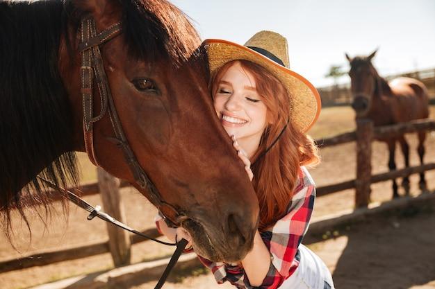 Happy cowgirl jeune femme tendre debout et serrant son cheval
