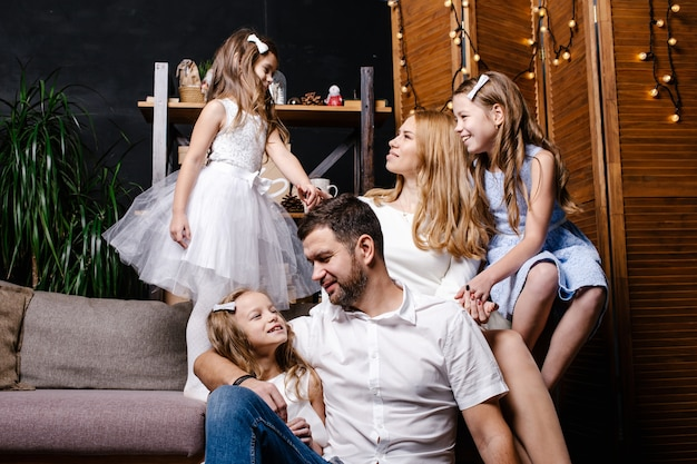 Happy cute family avec trois enfants échangeant des cadeaux sous l'arbre de noël sur le tapis