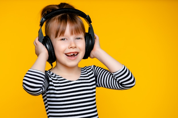 Happy cute girl child 5-6 ans avec un casque sur un mur jaune