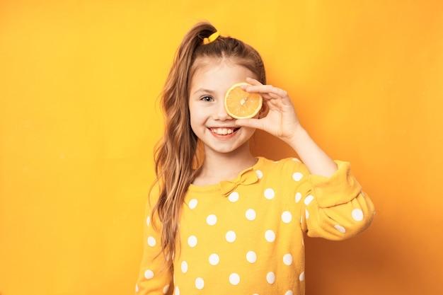 Happy cute girl holding citron sur les yeux sur fond isolé jaune avec un visage heureux debout et souriant avec un sourire confiant montrant les dents