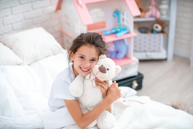 Happy cute girl sitting on the bed in her children room and hugs teddy bear.