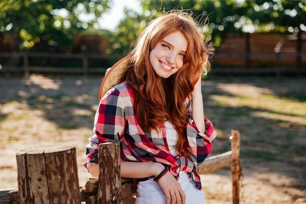 Happy cute young woman cowgirl debout et souriant à la ferme