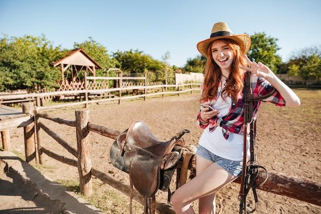 Happy cute young woman cowgirl avec téléphone portable debout et montrant le signe de la paix
