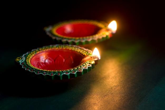 Happy diwali - lampes clay diya allumées pendant la célébration de diwali. conception de cartes de voeux du festival indien de lumière hindoue appelé diwali