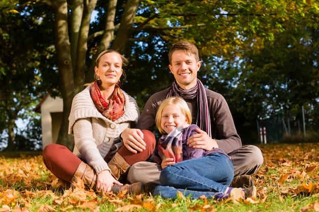 Happy family à l'extérieur assis sur l'herbe en automne