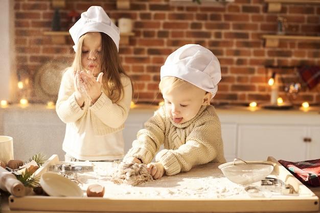 Happy family funny kids prépare la pâte, joue avec de la farine dans la cuisine