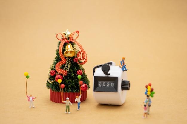 Happy family miniature personnes debout sur l'arbre de noël célébrez noël