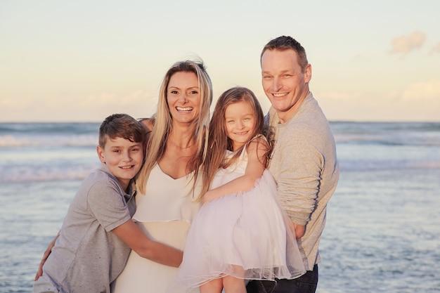 Happy family of quatre portrait sur la plage
