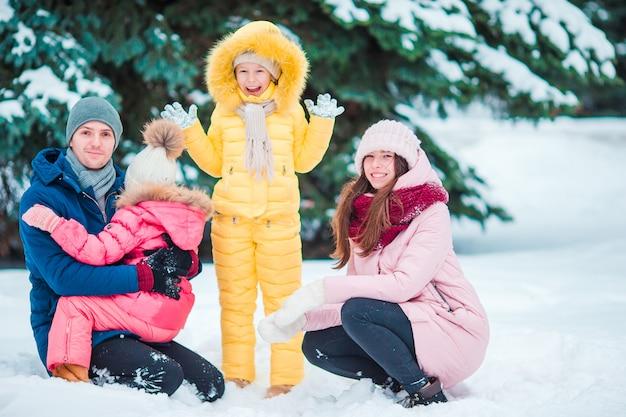 Happy family profiter de la journée d'hiver enneigée